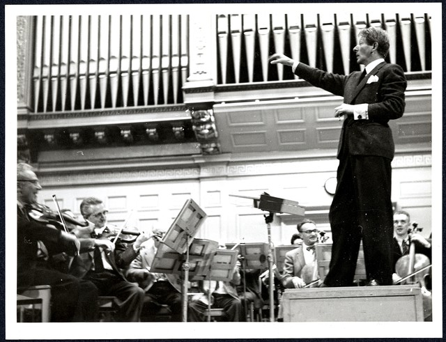 [ Danny Kaye, at right, stands in profile on podium, his right arm raised, conducting the Boston Symphony Orchestra, 1950s]