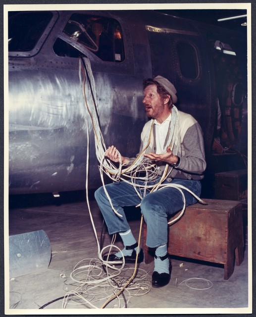 [ Danny Kaye, covered in wires, sits next to a jet airplane being assembled]
