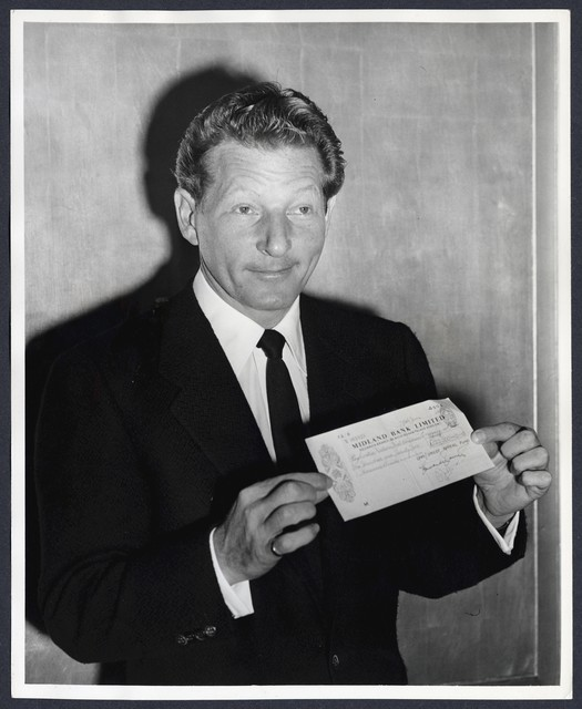 Danny Kaye holding cheque for £122,000