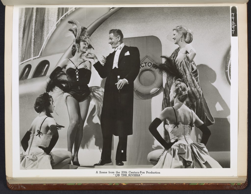 "[ Danny Kaye in theatrical impersonation of the character Henri Duran, gesturing toward an actress - scene from ""On the Riviera""]"
