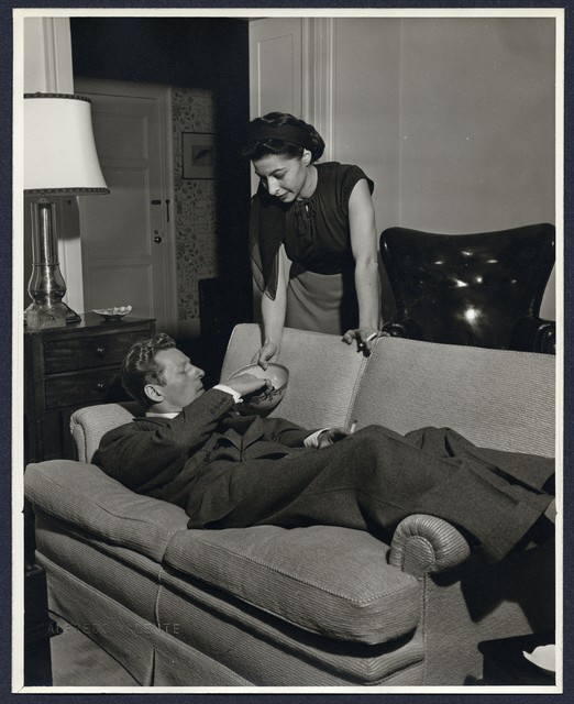[ Danny Kaye lies on sofa at home and Sylvia Fine offers him a bowl of snacks]