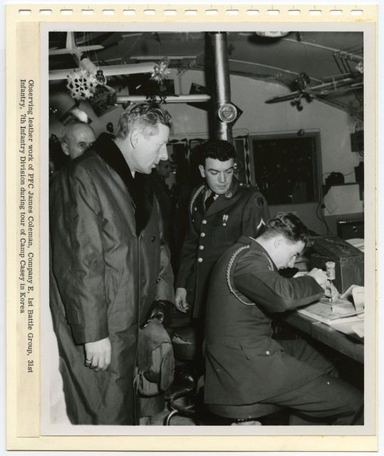 [ Danny Kaye] observing leather work of PFC James Coleman, Company E, 1st Battle Group, 31st Infantry, 7th Infantry Division during tour of Camp Casey in Korea