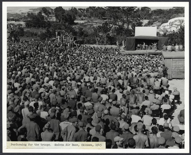 [ Danny Kaye on stage in distance conducting small orchestra, his back to audience of soldiers] Performing for the troops. Kadena Air Base, Okinawa, 1945