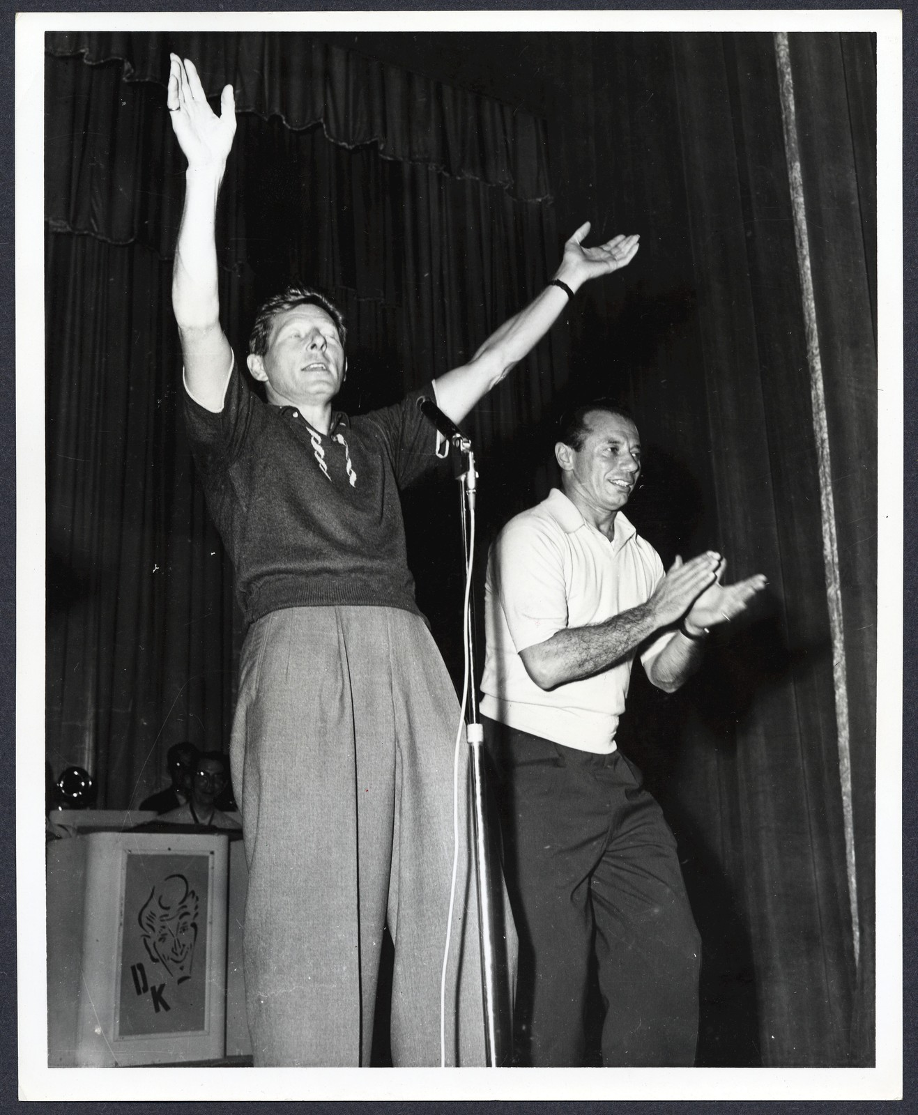 [ Danny Kaye, onstage, his eyes closed and arms raised, and unknown man clapping]