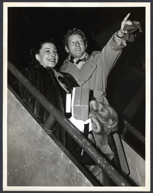 [ Danny Kaye points upward as he and Sylvia Fine disembark from airplane at night (in London for the Command Performance)]