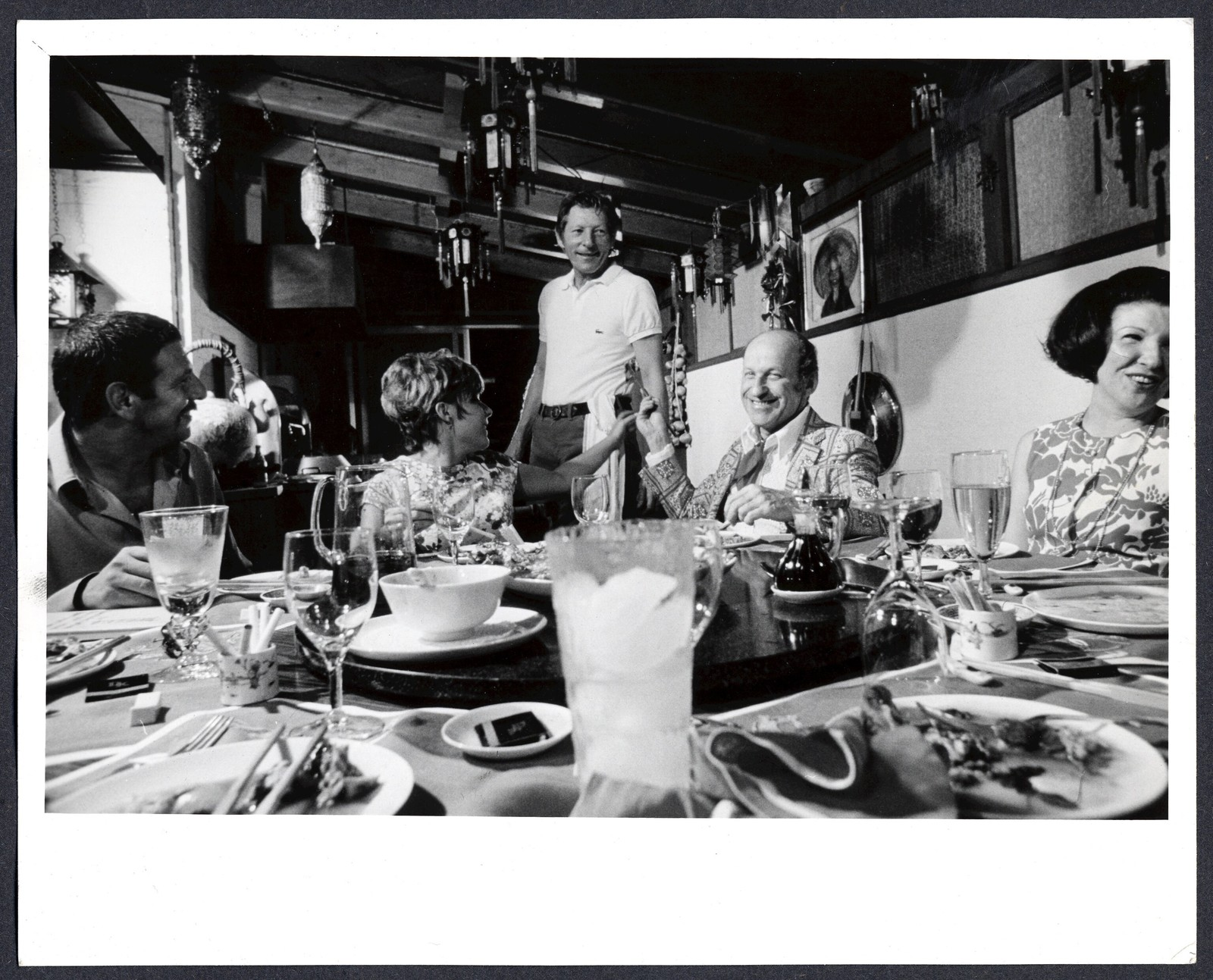 [ Danny Kaye serves guests in his Chinese kitchen. Dena Kaye seated in the middle]