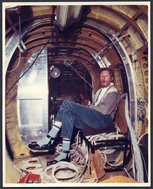 [ Danny Kaye sits among wires inside a jet airplane that is being assembled]