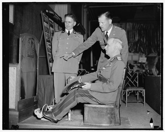 Demonstrate aviator's tester at Military Surgeons and Pharmacists Congress. Washington, D.C., May 8. Lieut. Ugo Reitano, army medical corps member from Italy, Capt. C.L. Leedhorn of the U.S. School of Aviation, look on while General Constantine Iliescu of Roumania tries out the latest U.S. Army mechanical tester for reaction of airplane pilots. The machine sets up theoretical problems for the pilot and test his reaction to each, thus eliminating hours of expensive tests by other methods