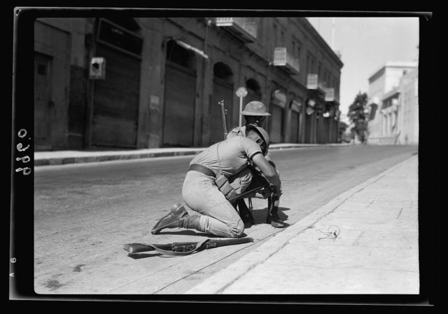 Deserted Jaffa Road showing troops laying telephone wire along the highway [Jerusalem]