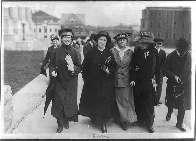 [Elizabeth Gurley Flynn , Dr. Mary Engi(?), R. Marsh(?), and Helen Schuster walking side by side on sidewalk]