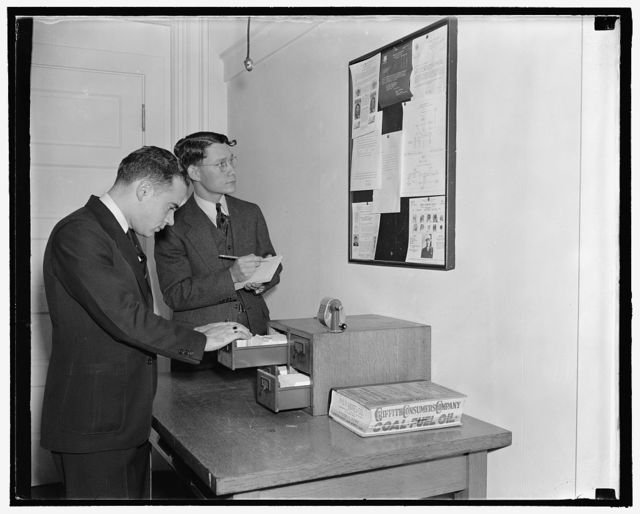 Employees of the Secret Service checking over bulletin board getting the latest criminal news, 10/38