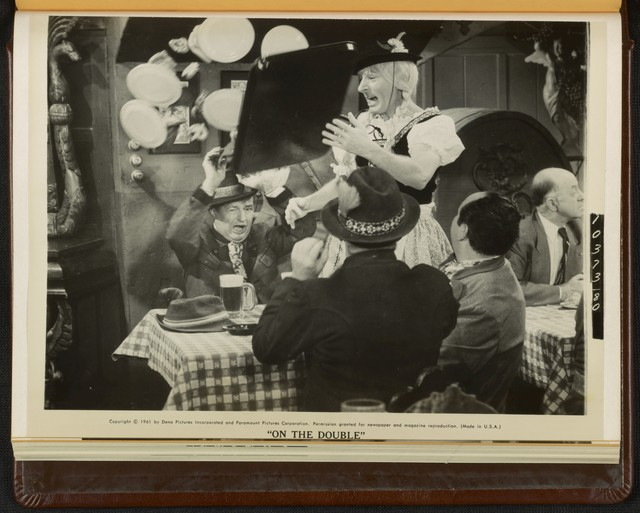 """[ Ernie Williams (Danny Kaye) dressed as a German waitress escapes from Nazi soldiers in a scene from """"On the Double""""]"""