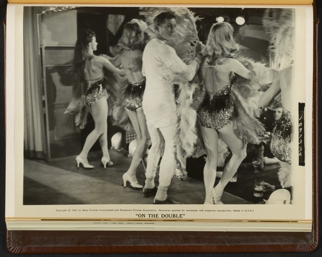 """[ Ernie Williams (Danny Kaye) hides behind German burlesque dancers while escaping from Nazi soldiers in a scene from """"On the Double""""]"""