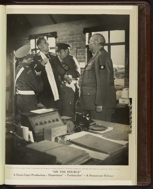 """[ Ernie Williams (Danny Kaye) is brought to General Willingham (Rex Evans) by MPs in a scene from """"On the Double""""]"""