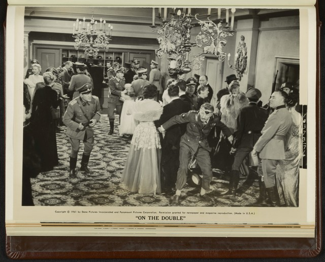 """[ Ernie Williams (Danny Kaye) runs through a party while escaping from Nazi soldiers in a scene from """"On the Double""""]"""