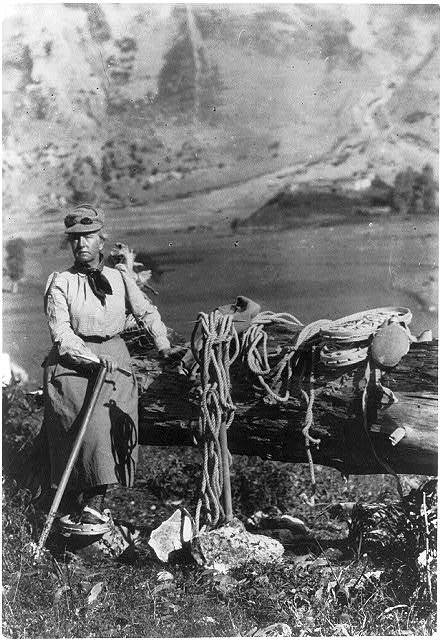 [Fannie Bullock Workman posed on mountain with mountain climbing gear]