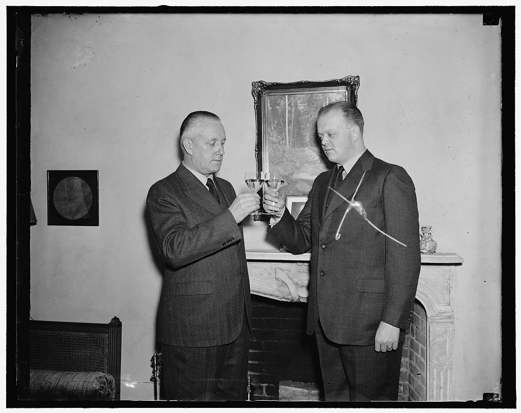 Finland drinks a toast. Washington, D.C., Dec. 15. Open House was the order of the day today at the Legation of Finland here. Toasts were drunk to the health of their President Pehr Evind Svinhufvudt [Svinhufvud], who is celebrating his 75th birthday today; Finland also paid her war debt installment due today to the United States, the only debtor nation to do so, which was another reason to rejoice. Pictured here are Dr. Eero Jarnefelt, (left) Finland Minister to the United States, and Dr. Sigurd Von Numers, Secretary of the Legation