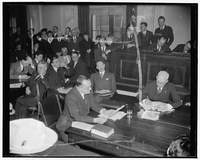 Frankfurter Counsel listens to testimony opposing appointment of Harvard professor. Washington, D.C., Jan. 10. Dean Acheson, right, former Undersecretary of the Treasury, as counsel for Prof. Felix Frankfurter, listens to testimony opposing his client's appointment to the Supreme Court before the Senate Judiciary Subcommittee today. George E. Sullivan, left, Washington Attorney and author, opposed the nomination on the grounds that Frankfurter was alien born--in Austria--and had 'alien affiliations.' 1/10/39
