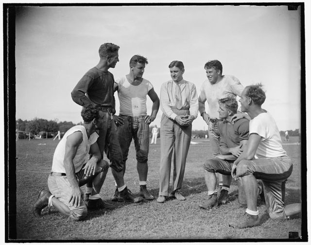 George Marshall, owner of the Washington Redskins, talks it over with some of his players, left to right: Wayne Millner, tackle, end, Charlie Malone, end,. Vic Carroll, Tackle,. George Marshall, Bill Young, Tackle, Ed Michaels, Guard, Jim Garber, Tackle,. 9/11/37