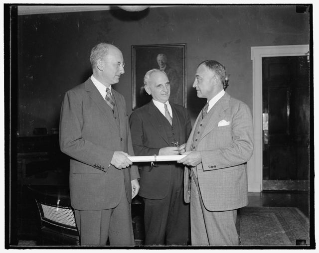 Gets new post in Bureau of Internal Revenue. Washington, D.C., Sept. 20. Secretary Henry Morgenthau presenting to John Philip Wenchel a commission as Assistant General Commission for the Bureau of Internal Revenue, succeeding Morrison Shafroth, resigned. Herman Oliphant, General Counsel for the Treasury is shown in center. A graduate of the University of Maryland, Wenchel has been in the Government Service for 23 years. 9/20/37