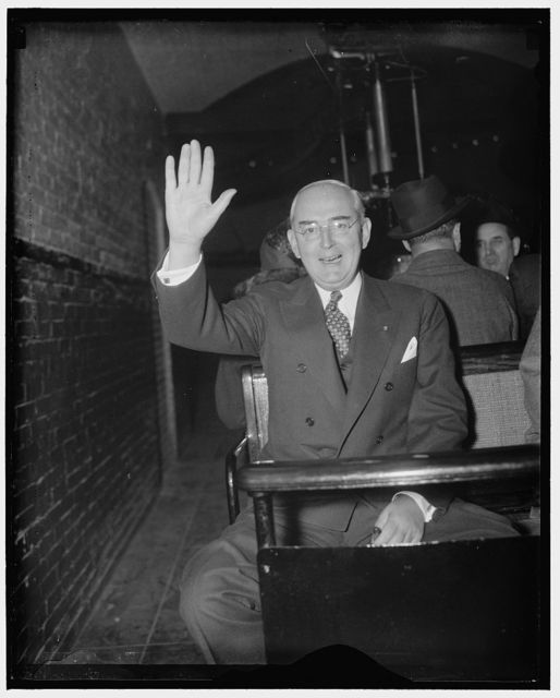 Happy Michigan Solon. Washington, D.C., Jan. 5. Among the few left, Republican Senator Arthur H. Vandenberg, of Michigan salutes the camera man as he uses the tram for the trip from the Senate Office building to Capitol for the opening session