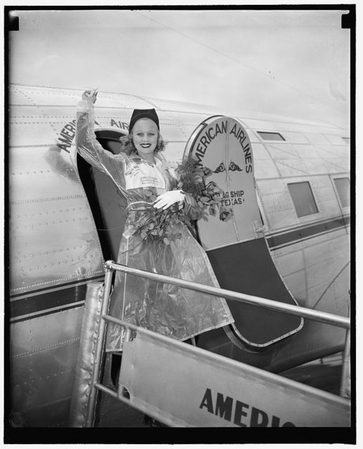 """Hollywood starlet arrives to participate in National Airmail Week. Washington, D.C., May 15. Miss Marion Weldon, Paramount starlet, waves a greeting to the throng as she arrived at Washington Airport today to participate in National Airmail Week as a representative of the film city. Miss Weldon was selected for the honor by the 22 pilots and stunt men who appeared with her in the forthcoming Paramount technicolor production """"Men with Wings,"""" 5/15/38"""