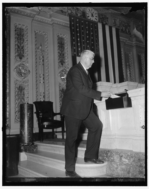 House hopper receives Bill No. 1. Washington, D.C., Dec. 30. Rep. Louis Ludlow, of Indiana putting House bill no. 1 into the hopper on the floor of the House today. The bill, which Rep. Ludlow is sponsoring at the investigation of the Fraternal order of Eagles, is designated to aid in the stabilization of employment in Commerce, Industry and Agriculture, the bonus bill was no. 1 on the House calendar last year