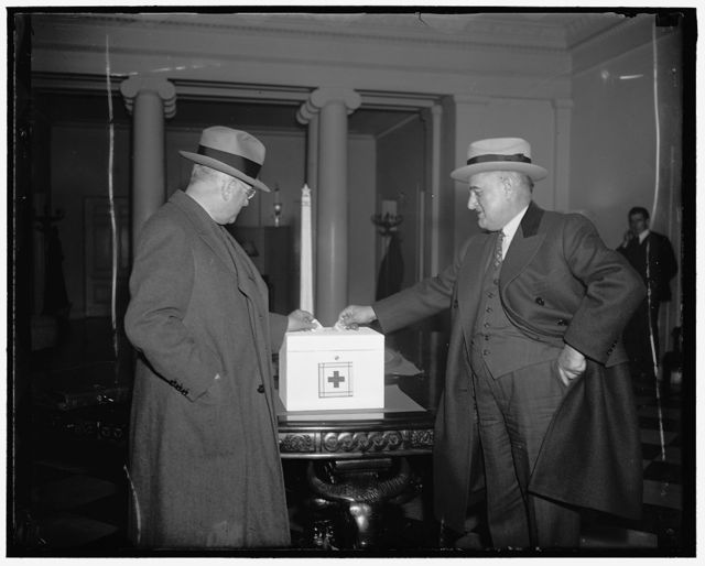 Ickes and Senator Guffey drop contributions in flood relief box at White House. Washington D.C. Callers on President Roosevelt today were reminded of the public's problem in the flood situation. A white enameled chest, about the size of a bread box, was put on a table in the lobby of the executive offices to receive flood contributions. Secretary of Interior Harold Ickes (left) and Senator Joseph Guffey, of Pennsylvania, pictured as they drop their contributions in the box