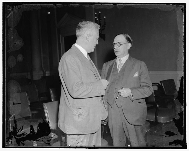In spotlight as house committee considers tax revision. Washington, D.C., Nov. 4. Lovell Parker, (right) tax expert of the Treasury, appeared before the House Ways and Means Sub-Committee today as it began consideration of a general revision of the Federal Revenue Structure. Parker is shown talking to Rep. Frank H. Buck of California, a member of the committee who reported today that he has found wide-spread opposition to the revision of the undistributed profits tax, chiefly because it prevents new corporations from organizing, hampers expansion by old ones, and fail to provide an exemption cushion for those suffering from debt. 11/4/37