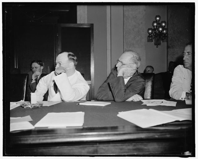Interested listeners. Washington, D.C., July 19. Senators Francis T. Maloney, Left, Connecticut, and George L. Radcliffe, Maryland, lend an attentive ear to the testimony of Marriner Eccles, Chairman of the Federal Reserve Board, before the Senate Banking and Currency Committee today. Eccles told the committee the president's lending program is the only immediately practicable means of stimulating business and employment up to prosperity, 7/19/39