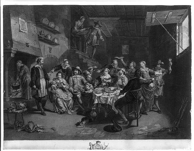 [Interior scene with group gathered around table eating and drinking, large hearth at left]