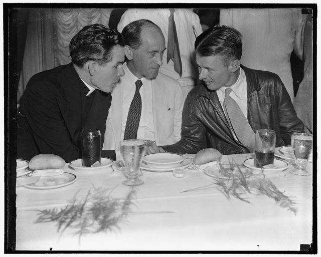 "Irish get together with Corrigan Washington, D.C., Aug. 10. Doug ""Wrong Way"" Corrigan, honor guest of the Ancient Order of the Hibernians at the Willard Hotel, sits down to luncheon with Rev. Sheehan, (left) and Charge D'Affairs of the Irish Legation Robert Patrick Brennan, 8/10/38"