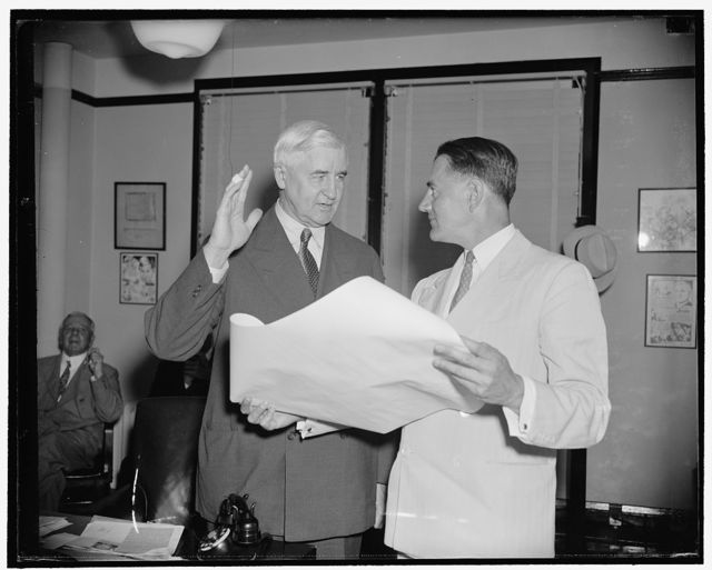 Jesse Jones takes oath as Federal Loan Administrator. Washington, D.C., July 17. Jesse Jones, retiring Chairman of the RFC today was sworn in as Federal Loan Administrator by Ronald H. Allen, right, Assistant Secretary of the RFC