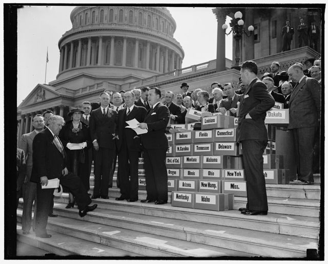 """Keep America Out of War"" petitions presented to Congress. Washington, D.C., April 27. ""Keep America Out of War"" was keynote of four million petitions presented to members of Congress at the Capitol today by the veterans of Foreign Wars. Senator Key Pittman as President Pro Tempore of the Senate, received the petitions for the Senate. In the photograph, left to right, can be seen: Senator Pat McCarran, Nevada; Mrs Laurie M. Schertle, Nat. President, Ladies Auxiliary, Veterans of Foreign Wars; Senator Key Pittmen; Speaker of the House William D. Bankhead; and Scott P. Squires, Commander-in-Chief of Veterans of Foreign Wars"