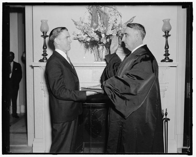 Kentucky Solon takes oath as Justice of D.C. Court of Appeals. Washington, D.C., May 12. Former representative Fred. M. Vinson, of Kentucky, being sworn in as an Associate Justice of the District of Columbia Court of Appeals today by Joseph W. Stewart, clerk of the Court. Judge Vinson was appointed last year by President Roosevelt with the understanding that he would continue in the House until the Tax bill was enacted, 5/12/38