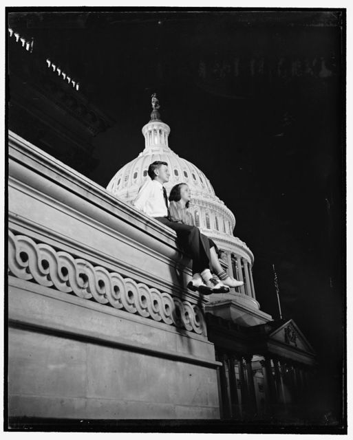 Light in Capitol dome means pages have to work at night. Washington, D.C., July 1. When the light is burning in the dome of the Capitol, it signifies that Congress is holding a night session. To pages, this means night work- no dates. Democratic Page of the House Mac Arnold is here looking glum with Helen Rodis over the prospect of night work while the House works on the Bloom Neutrality Bill