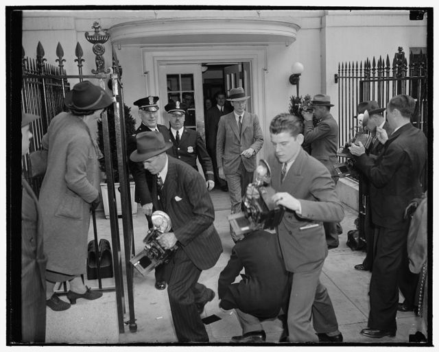 Lindbergh stymied by photographers. Washington, D.C., April 20. Camera-shy Col. Charles A. Lindbergh leaving the White House after a conference with President Roosevelt today, found all exits well 'covered' by news cameramen. Here we see the famous flyer running the photographer's gauntlet as he emerged from a side door of the Executive Mansion