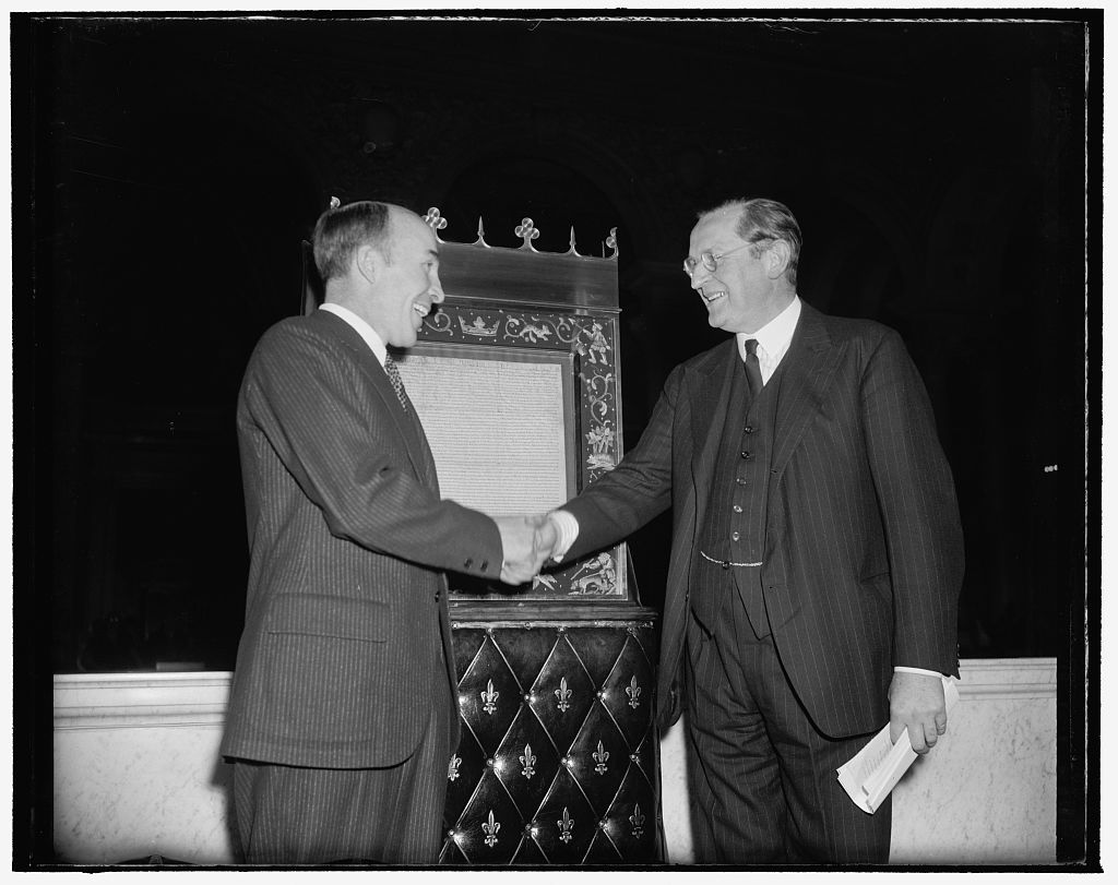 Magna Carta deposited in Congressional Library for duration of war. Washington, D.C., Nov. 28. The most cherished existing copy of the Magna Carta was today deposited in the Congressional Library here for the duration of the war by British Ambassador Lord Lothian. Librarian Archibald MacLeish, left, is shown thanking Lord Lothian after accepting the document which can be seen in the background. The Magna Carta will be on display for the public in a spot opposite the Declaration of Independence and the Constitution
