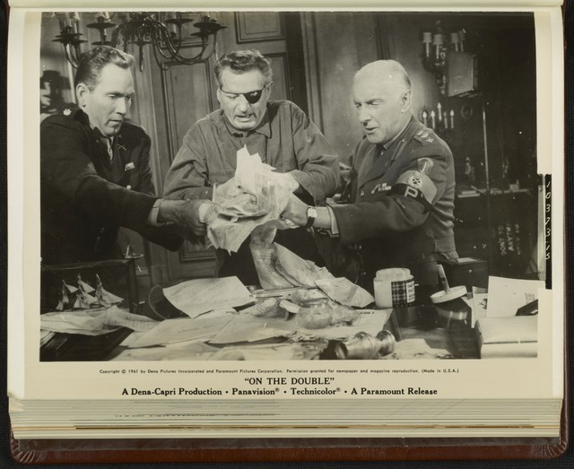"[ Major Houston (Gregory Walcott), Ernie Williams (Danny Kaye), and Colonel Somerset (Wilfrid Hyde-White) try to remove papers from Ernie's hands in a scene from ""On the Double""]"