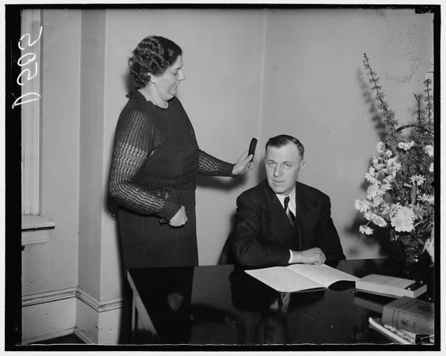 Making the boss ready. Washington, D.C., Jan. 7. Rep. Michael Kirwan, new Democratic member of the House from Ohio, is given the final touch from his Secretary, Mrs. Roberta Messerly, before posing for the cameramen