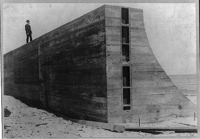 [Man standing on portion of seawall built after the hurricane and flood of 1900, Galveston, Texas]