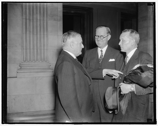 Maritime head urges stabilization of employer-employee relationship . Washington, D.C., Dec. 8. Appearing before the Senate Education- Labor and Commerce Committees today, Chairman Joseph P. Kennedy of the U.S. Maritime Commission, urged stabilization of employer-employee relationship in the Merchant Marine through application of principles of the Railway Labor Act. Left to right: Senator Joseph F. Guffy of Pennsylvania; Joseph P. Kennedy; and Admiral Emory S. Land, also a member of the Maritime Commission. 12/8/37