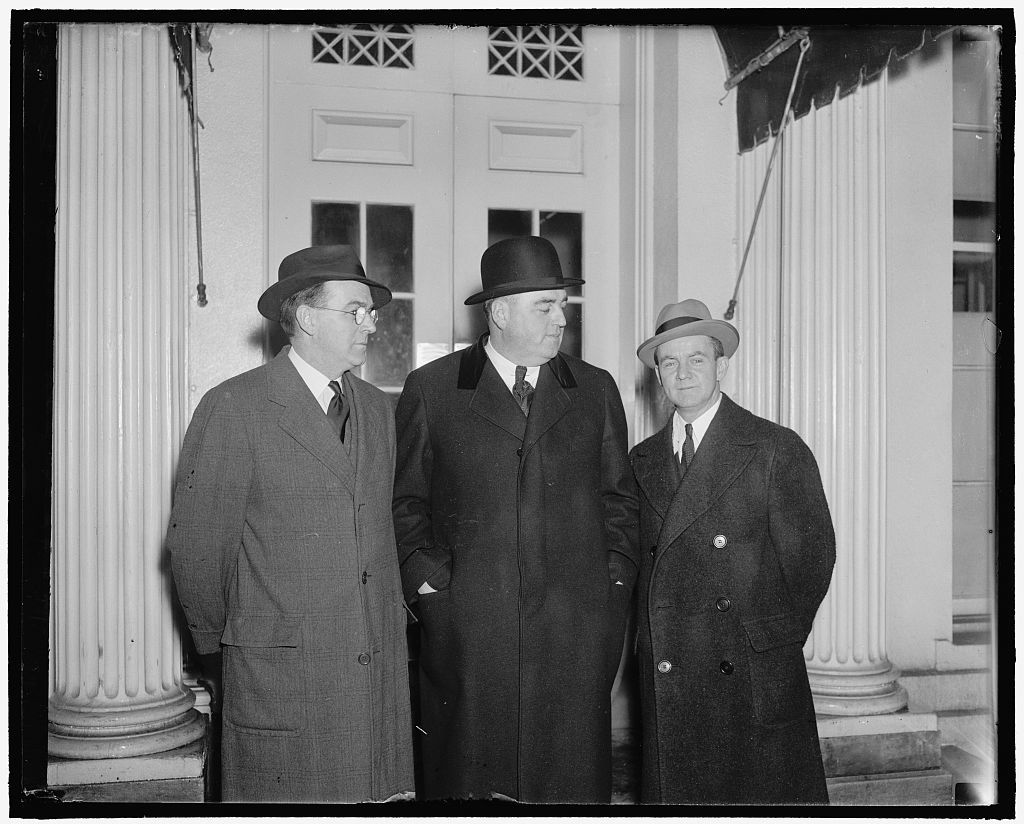 Massachusetts governor protests proposed trade pact with Great Britain. Washington, D.C., March 16. Governor Charles F. Hurley, (center) of Massachusetts, arriving at the White House where he left a protest with President Roosevelt against the proposed trade pact with Great Britain. Hurley said if the pact is effected it will do serious damage to the textile industry in his state. On the left is Raymond Fitzgerald, Secretary to the Governor, and on right, William J. Moore, Attorney General of Massachusetts