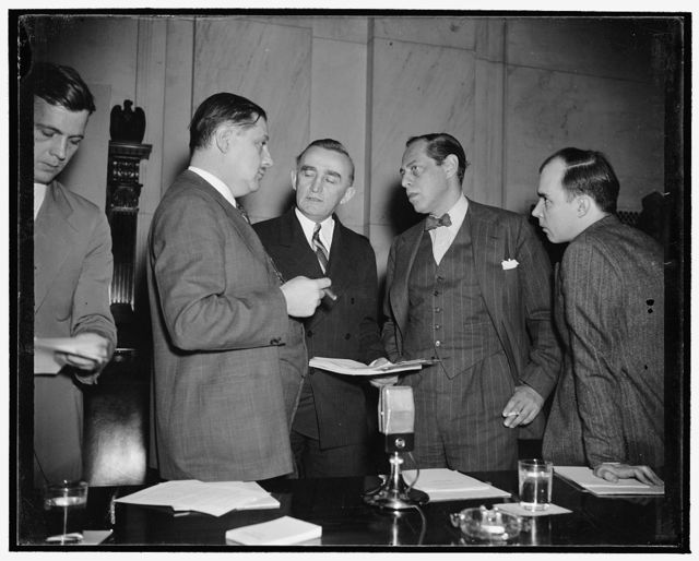 Monopoly huddle. Washington, D.C., Dec. 12. At this informal conference just before the Monopoly Committee opened today's hearing can be seen, left to right: Assistant Attorney General Thurman Arnold, Chairman Joseph C. O'Mahoney, S.E.C. Commissioner Jerome Frank, and Hugh B. Cox, Special Assistant to the Attorney General. In opening today's hearing on the glass industry's patent policies, Cox said the Justice Department seeks to disclose the relation between patent laws and enforcement of anti-trust laws, 12/12/38