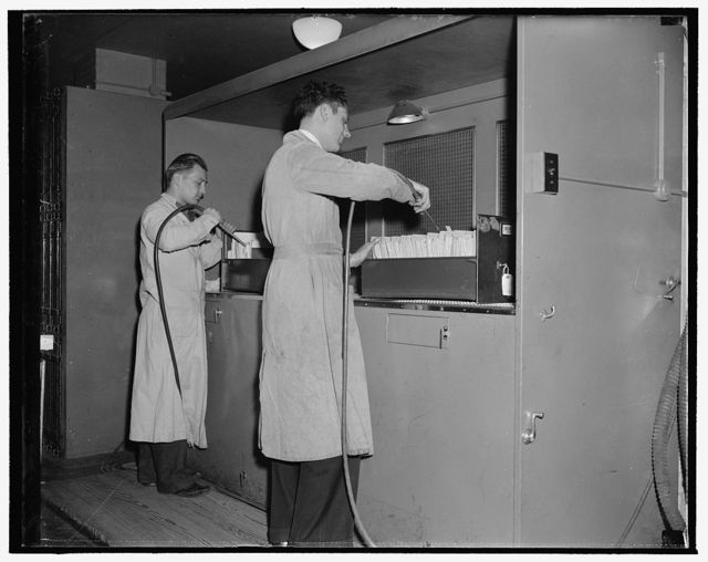 National Archives. Washington, D.C., Nov. 22. After leaving the gas chamber the documents are worked on by air blowers to eliminate all dust and foreign particles. The dust from the papers is carried out through the screen in the background into a purifier