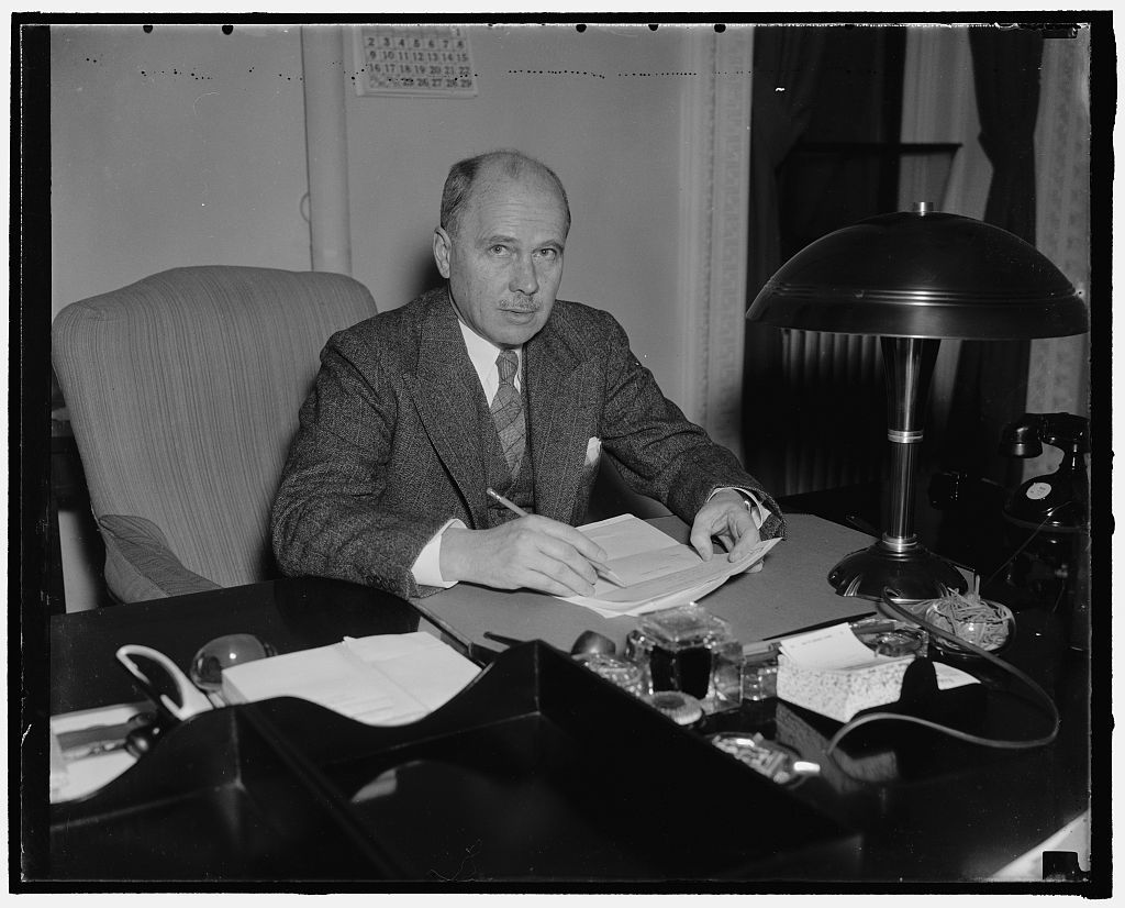 New Ambassador to Germany. Washington, D.C., Jan. 14. Hugh Wilson, former asst. sec. of State, and newly appoint ambassador to Germany replacing William E. Dodd, photographed at his desk at the State Department, 1/14/38