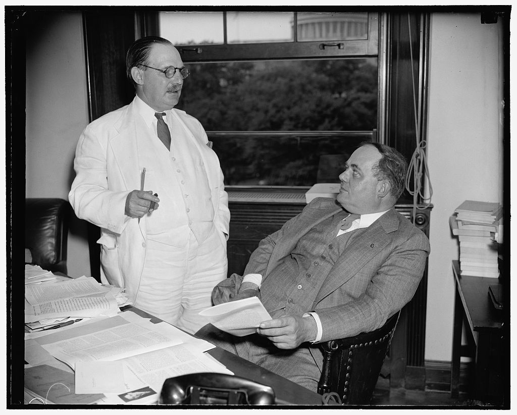 """New and retiring tax experts. Washington, D.C., June 10. Lovell H. Parker, (left) Chief of Staff of the Joint Congressional Committee on Internal Revenue Taxation who resigned today, is pictured with is successor C.F. Stam. Stam has served the Committee since 1927, and, recently as counsel. Chairman Harrison of the Senate Finance Committee, in announcing Parker's resignation, praised him as """"one of the greatest tax experts in America,"""" 6/10/38"""