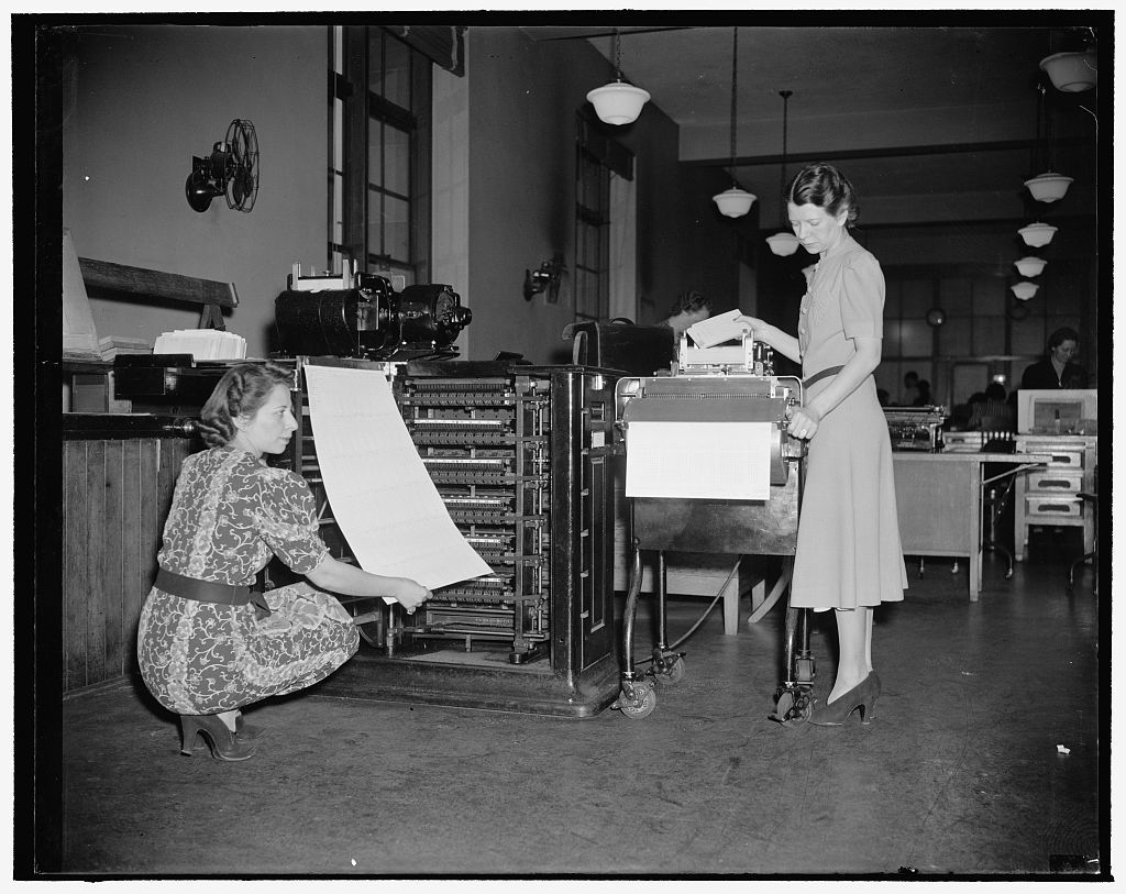 New machine to speed up statistics of census of 1940. Washington, D.C., Dec. 2. Back in 1870, it took 7 years to compile statistics from the facts taken by census takers, but in the next 10 years, Herman Hollerith invented a 'unit tabulator,' shown on left of photo being operated by Operator Ann Oliver. This machine is fed cards containing census information at the rate of 400 a minute and from these, 12 separate bits of statistical information is extracted. Not so long ago, Eugene M. La Boiteaux, Census Bureau inventor, turned out a smaller, more compact machine, which extracts 58 statistics from 150 cards per minute. This machine is shown on the right and is being operated by Virginia Balinger, Assistant Supervisor of the current Inquiry Section. With the aid of this machine, statistical information from the 1940 census is expected to be compiled in 2 1/2 years. The secret of the machine lies in the cards. The written information taken by census takers is brought in and the data translated into code numbers which are punched on the card, and the legible data is locked up in vaults away from prying eyes. Cards are fed into the machine, sensitive steel fingers feel out the punches, set up electrical impulses, and in no time at all, the card has set down on the large sheet just what statistic from each individual goes in what place