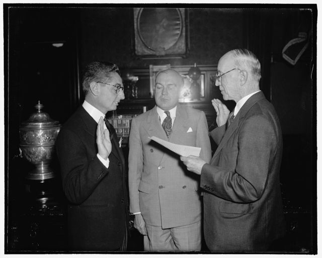 New Philippine Resident Commissioner takes Oath of Office. Washington, D.C., Sept. 30. Joaquin M. Elizade, (left) newly appointed Philippine Resident Commissioner, is pictured as he administered the Oath of Office today by Frank M. Hoadley, Assistant Chief Clerk of the War Department. Secretary of War Harry H. Woodring is shown in the center. Elizalde succeeds Quitin Paredes, whose resignation was recently accepted by President Manuel Quezon, 9/30/38