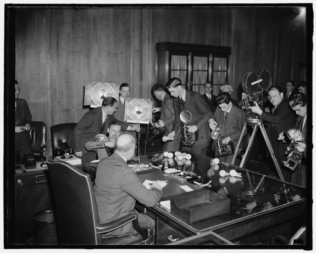 """New Supreme Court Nominee faces """"firing squad."""" Washington, D.C., Jan. 15. Shortly after his nomination to the Supreme Court bench was announced today by President Roosevelt, U.S. Solicitor General Stanley F. Reed faces this huge battery of cameras--both sounds and still--at his office in the Justice Department, 1/18/38"""